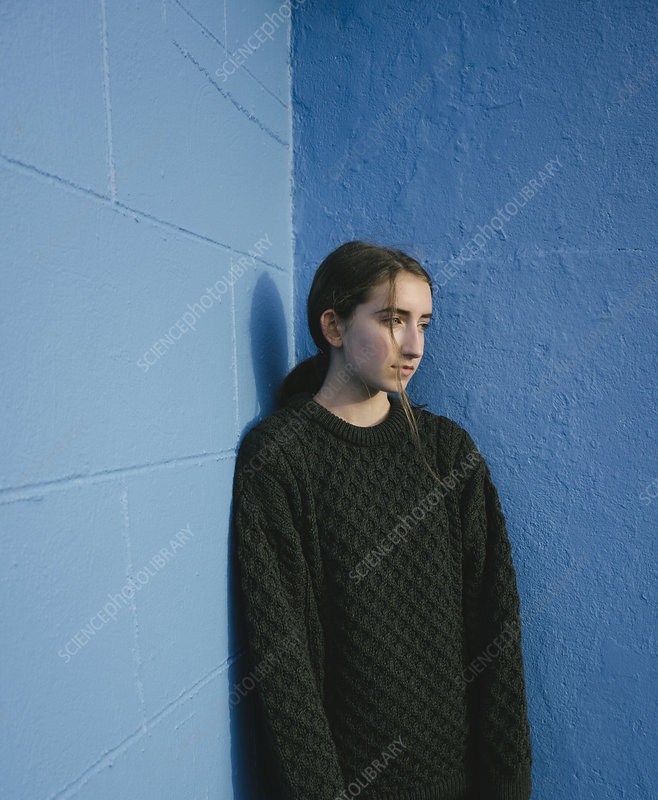 Teenage girl against blue wall