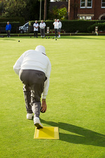 Lawn bowls player preparing bowl delivery