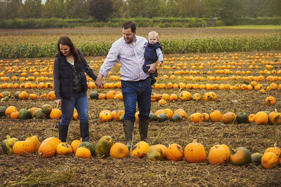Family among colourful pumpkin harvest