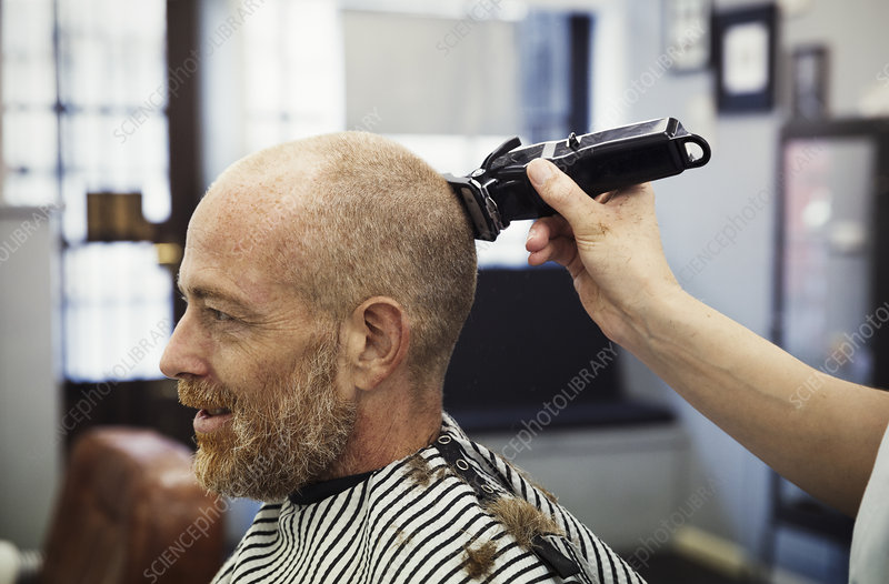 Barber shaving customer's head
