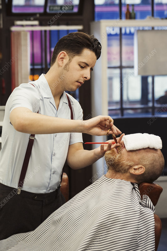 Barber trimming customer's beard