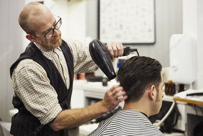 Barber blow-drying customer's hair