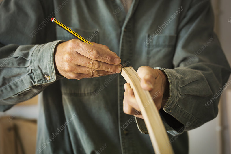 Craftsman marking a piece of curved wood