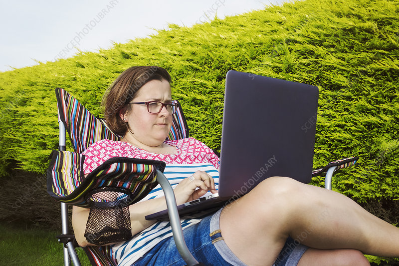 Woman in camping chair with laptop