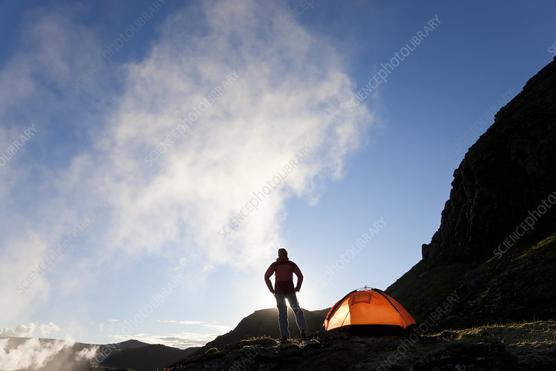 Woman next to tent at sunrise