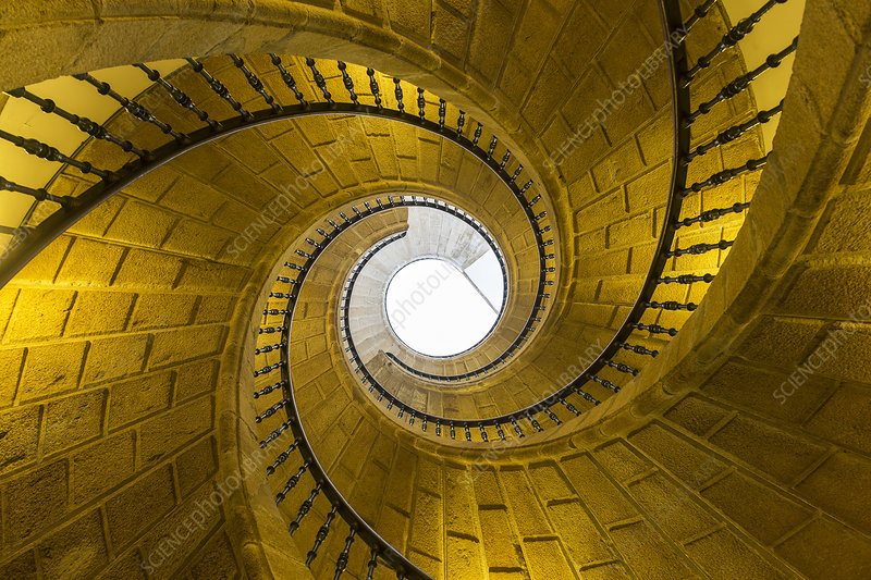 Low angle view of stone spiral staircase towards skylight