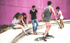 A group of young skateboarders in a skate park