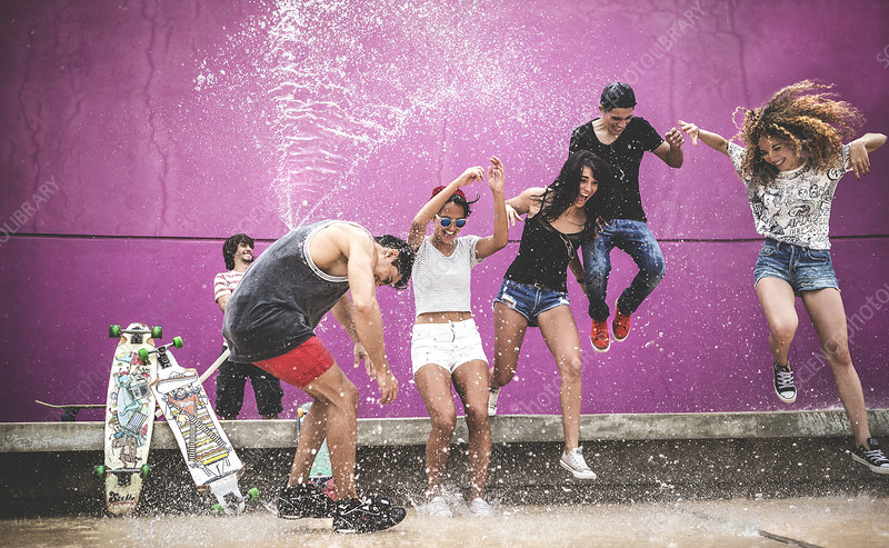 Young people jumping while being sprayed with water
