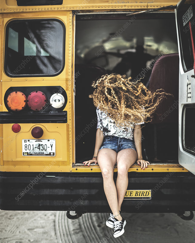 Young woman in tailgate of school bus