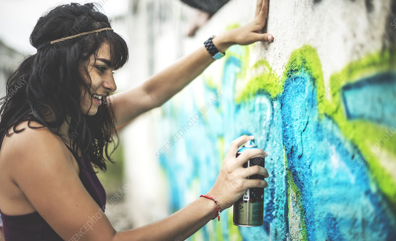 A young woman spray painting graffiti onto a wall
