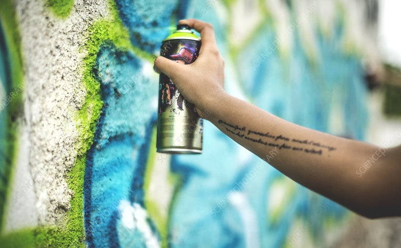 Close up person spray painting a graffiti tag onto a wall