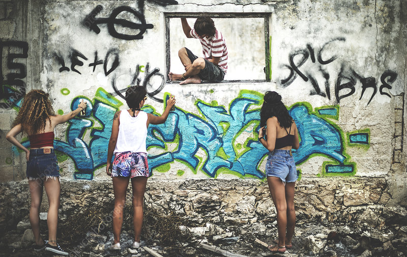 Four young people painting graffiti onto a derelict building