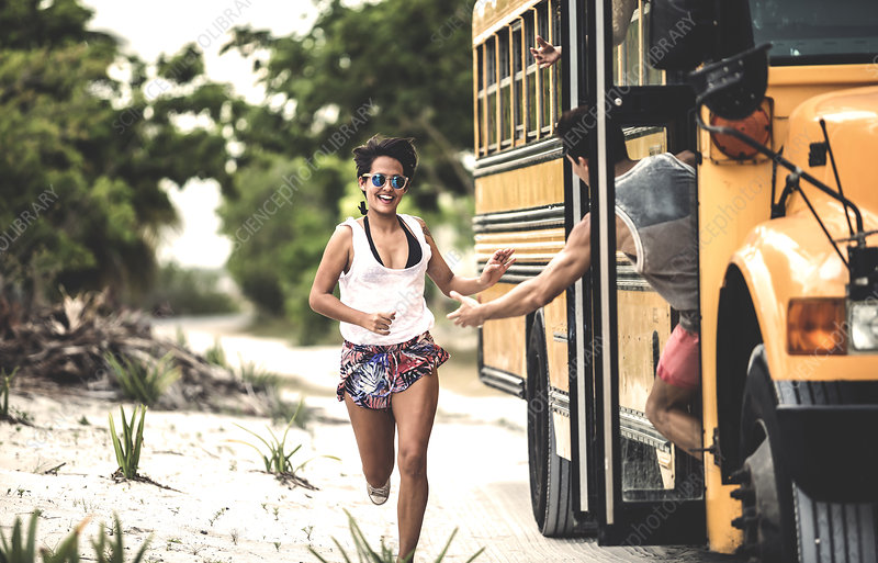 A young woman chasing after a moving school bus