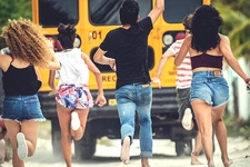 A group of young people chasing a moving school bus