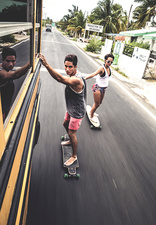 Two skateboarders holding on to moving school bus