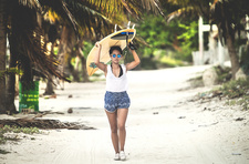 Young woman walking along a beach carrying a surfboard