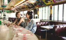 Two young women sitting at counter in diner