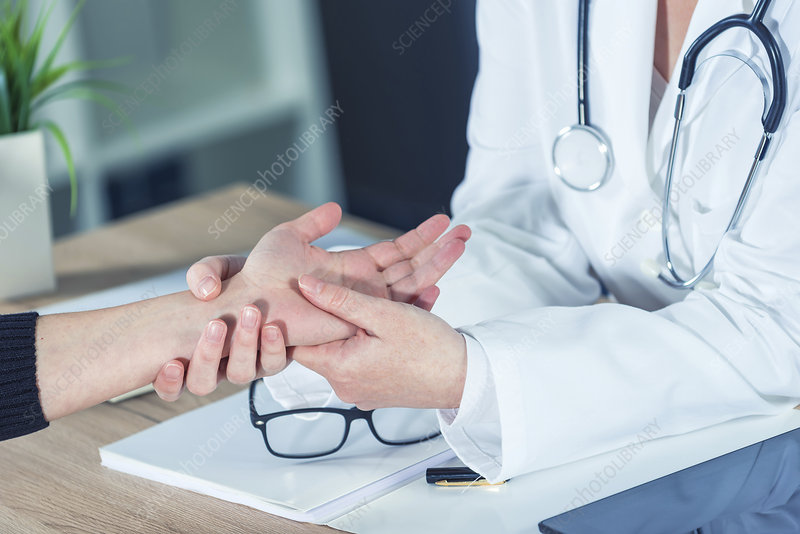 Doctor examining woman's wrist