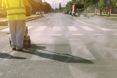 Worker painting pedestrian crossing