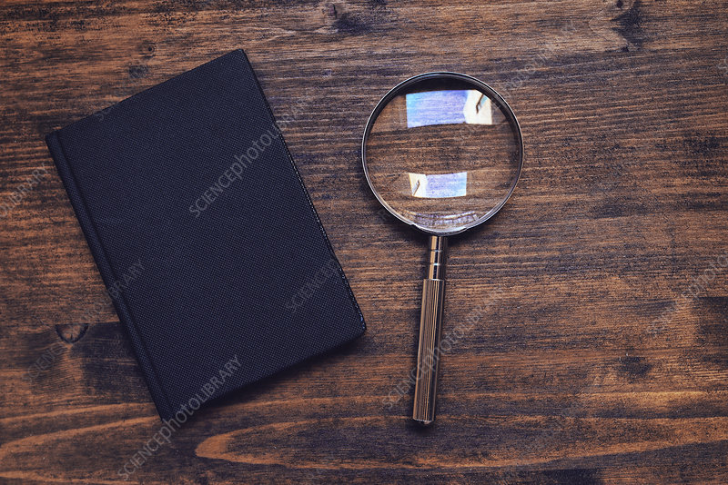 Magnifying glass and notebook on wooden desk