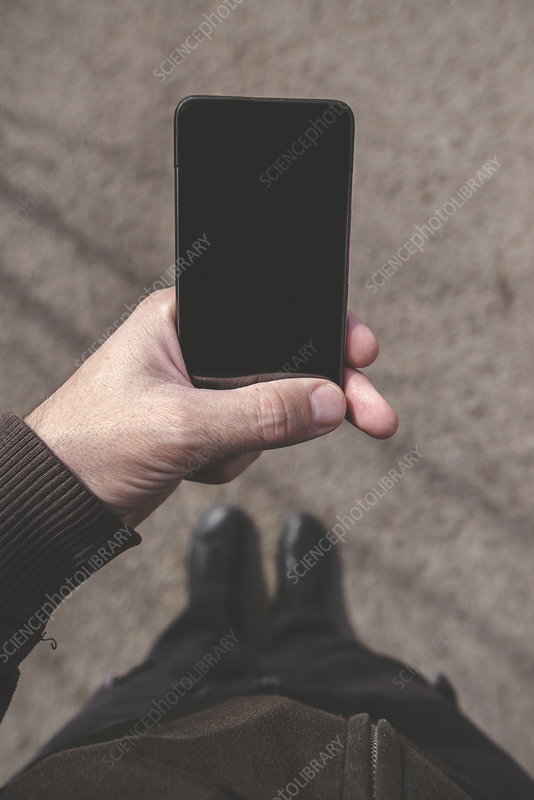 Man looking at smartphone screen on street