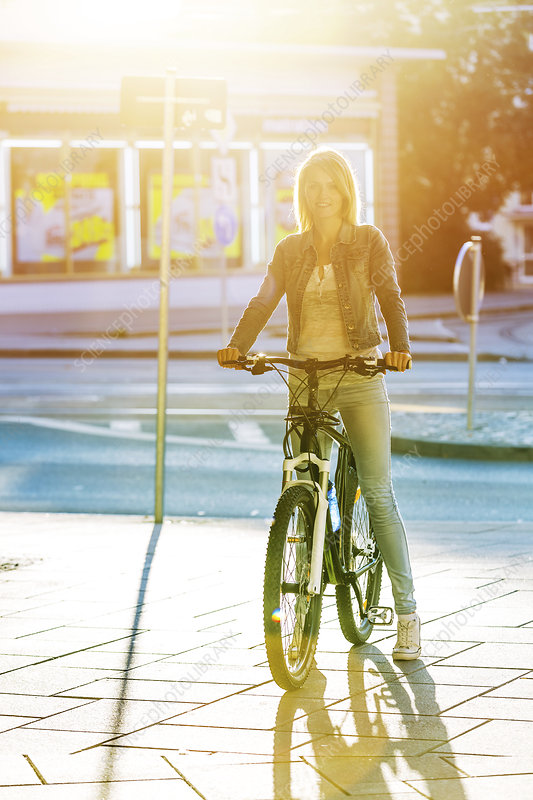 Young woman cycling in city