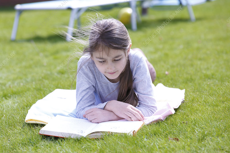 Girl lying on grass reading