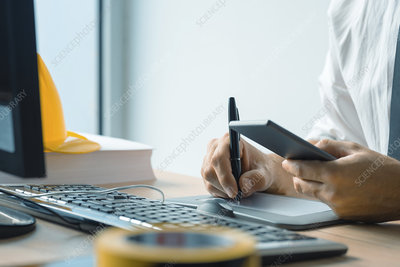 Worker using pen tablet and mobile phone
