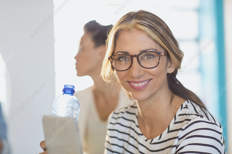 Businesswoman with digital tablet and water bottle