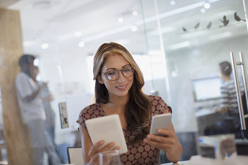 Businesswoman using smartphone and digital tablet