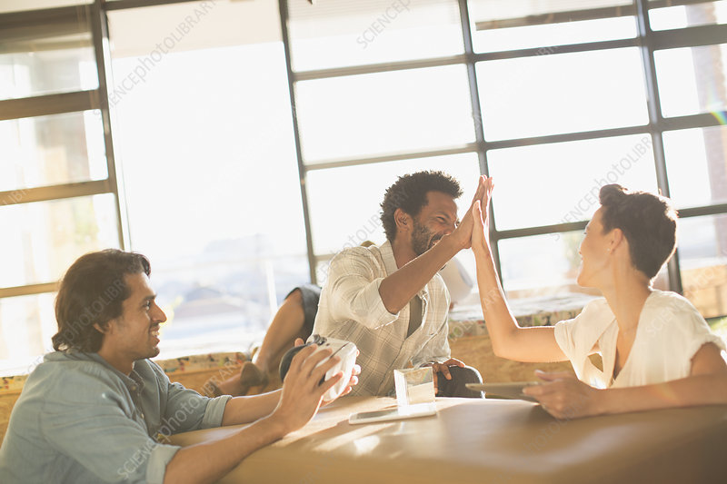 Excited entrepreneurs high-fiving meeting