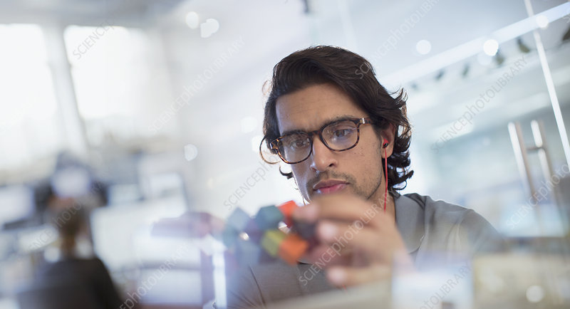 Focused, innovative male entrepreneur examining prototype