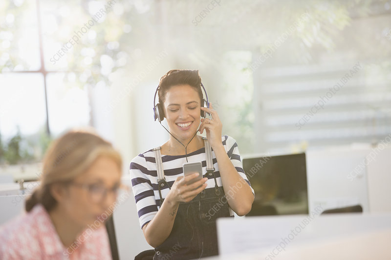 Businesswoman listening to music with smartphone