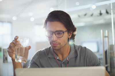 Businessman with headphones drinking water at laptop