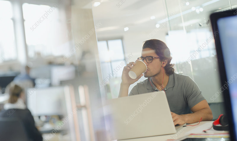 Businessman drinking coffee, working at laptop