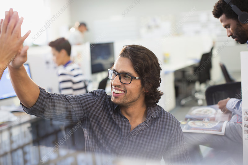 Businessman high-fiving with colleague