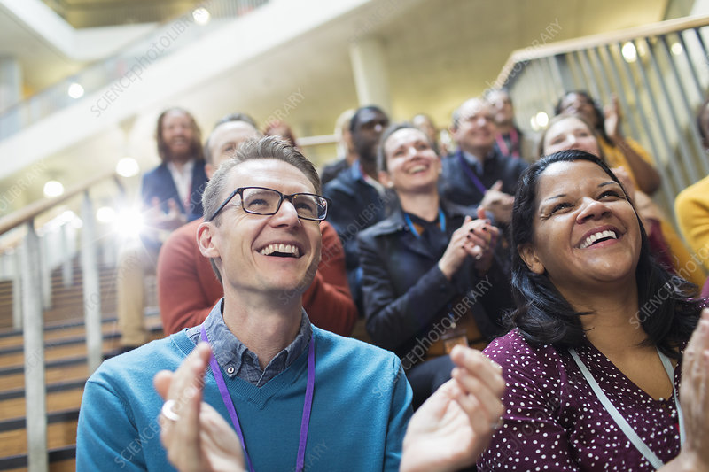 Laughing, happy conference audience clapping