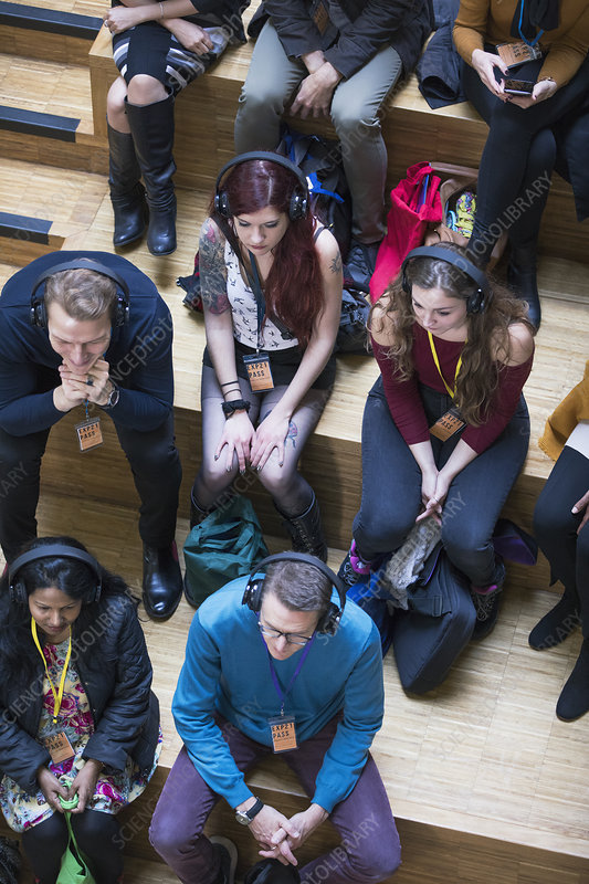 Overhead view audience listening with headphones