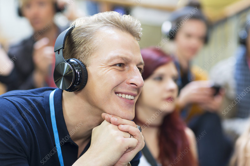Smiling businessman with headphones listening