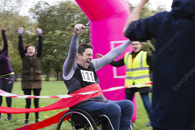 Man in wheelchair crossing race finish line