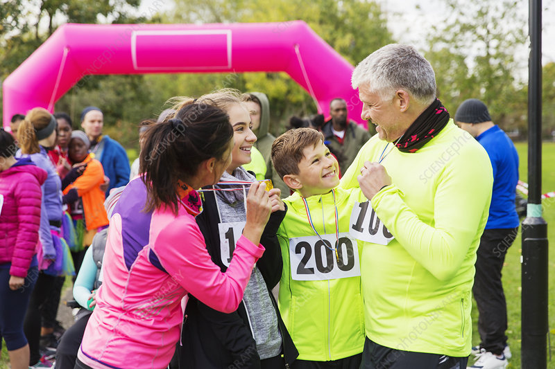 Happy family with medals finishing charity run