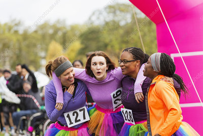 Happy female runners hugging finish line