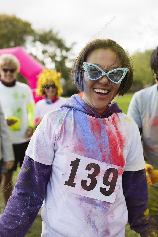 Portrait runner in sunglasses and Holi powder