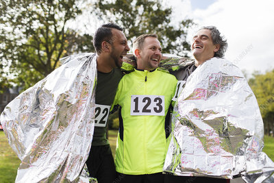 Happy marathon runners wrapping in thermal blanket