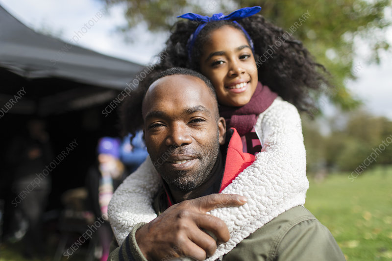 Portrait smiling father piggybacking daughter
