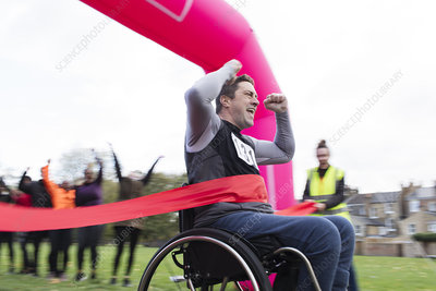 Man in wheelchair crossing finish line