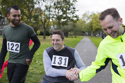 Runner shaking hands with friend in wheelchair