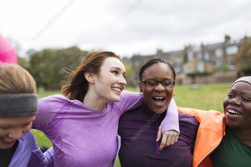 Happy female friends hugging in park