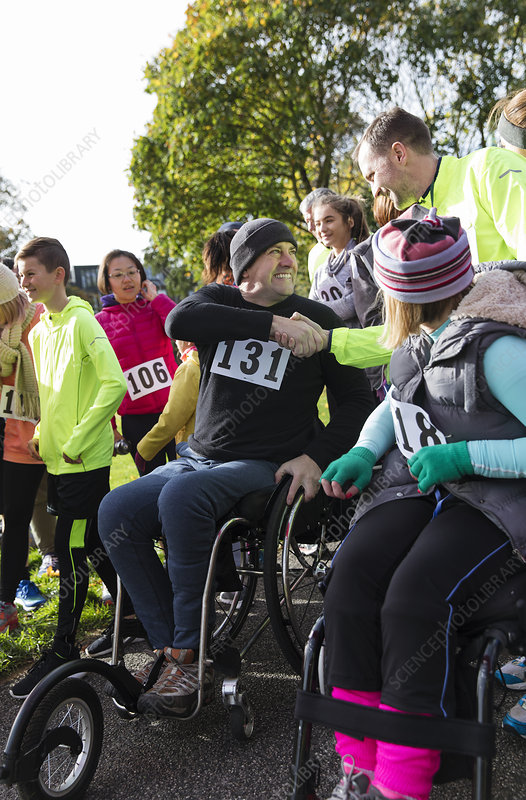 Man in wheelchair shaking hands with runner