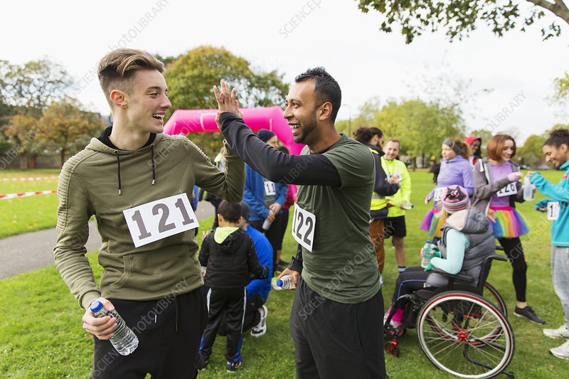 Male runner friends high-fiving after charity run